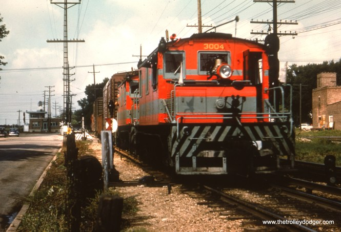 """#24 - WS: Locos #3003-3004 lead an E/B frt out of Wheaton. In backgound is the """"new"""" Dispatcher's Office. View looks west. (Another great pic — never seen this one before.)"""