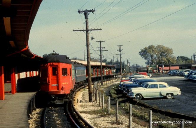 """#94 - JN: Train on outbound platform at Desplaines Ave. Note """"baldy"""" heading to Chicago in background. EM: CAE 401 (Pullman, 1923) leads a two car consist at the new (1953–1957) station on the west side of Des Plaines Av. At this time the CAE trains turned around without crossing Des Plaines Av. The CTA trains discharged all passengers at this station. Those who want to go further west boarded a CAE train here and paid another fare. The green and cream train in the background has just come from their station (color-coded green) on the other side of the loop where the CAE trains discharged all their passengers. Those wishing to continue east had to pay another fare to the CTA. the loops did not cross at grade, there was a wooden structure to carry the CTA trains above the tracks of the CAE. All the tracks east of Des Plaines Av, formerly owned by the CAE as far as Laramie Av, were sold to the CTA."""