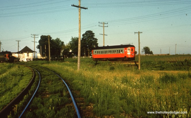 #58 - JN: Westbound train leaving Batavia Jct. EM: At Batavia Jct, formerly know as Eola Jct, a red and grey car heads for Aurora while the blue car at the station is ready to depart for Batavia. Looking SE.