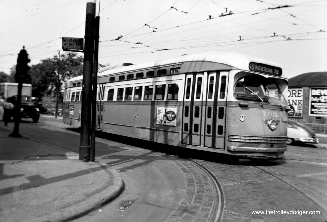 """Jeff Wien writes, """"PCC 7165 is a route 49 Western pullout from Devon Station (Clark and Schreiber). Car is pulling off of Clark onto Devon to head west and south along Western to 79th St. In back of photo one can see the wall of the Ridge Theater that later became a part of the Clark-Devon Hardware Store."""""""