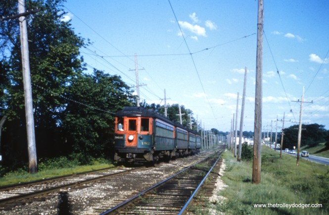 CNS&M 182 heads up an eastbound train at St. Mary's Road in the Thornbury Village subdivision (Glen Oaks,IL) on the Mundelein branch on May 31, 1962.