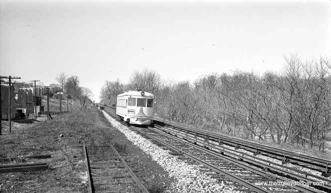 "An LVT 1000-series lightweight high-speed car on the Philadelphia & Western in the 1940s. According to Jim Graebner, the siding is ""a yard track of the Millbourne Mills shop area. The long straight stretch of double track leads to the first station stop at West Overbrook, which is just over the hill out of sight."""