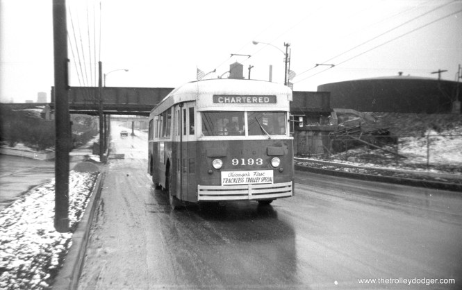 "CTA 9193 is on what is billed as ""Chicago's first trackless trolley special,"" March 2, 1958. Andre Kristopans: ""Trolleybus 9193 is on Kedzie just north of the Sanitary & Ship Canal (about 33rd). Bridge is IC Iowa Division, background bridge is Chicago & Illinois Western. Clue was the big tank to the right. 1938 aerial photo shows this tank. Note how little traffic there is on Sunday!"" The occasion was the very first Omnibus Society of America fantrip, which used a prewar trolley bus on south side areas where they had not been used in service."