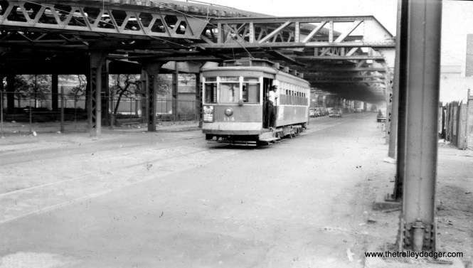 """CTA 114 heading east on 63rd street, just about to go under the Jackson Park branch of the """"L"""". M. E. adds, """"At the right side of the picture in the foreground are two vertical posts that supported the structure that went south across 63rd St. to the lower 63rd St. yard. Therefore this picture was taken just about underneath that structure."""" (Roy W. Bruce Photo)"""