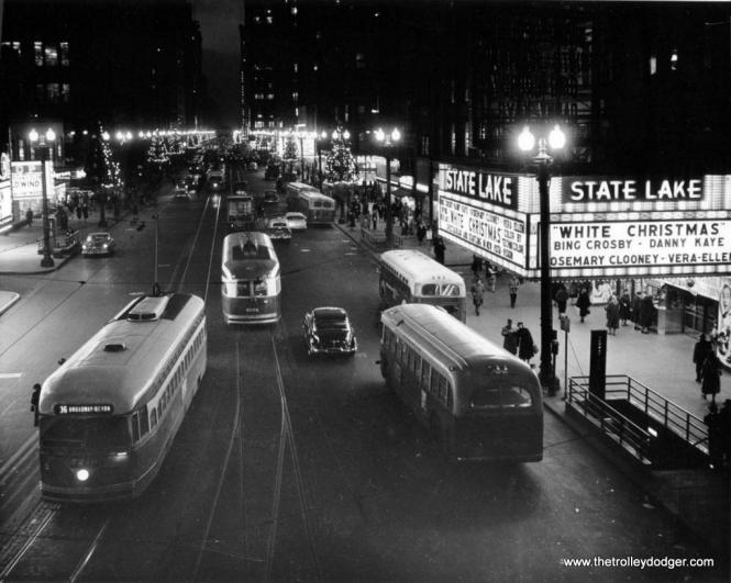 PCCs and buses share State Street in December 1954. The former State-Lake theater is now used by ABC station WLS-TV to tape live performances.