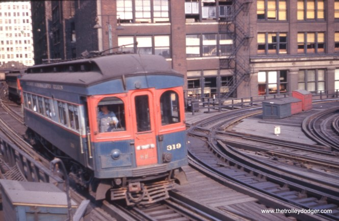 """Chicago, Aurora & Elgin wood car 319 heads west, having just left the CTA's Wells Street Terminal, sometime prior to the end of CA&E service downtown in September 1953. This was a stub-end terminal, and the tracks at right curved around to Van Buren and connected to the southwest corner of the Loop """"L"""". In 1955, that connecting track was removed as part of the construction of lower Wacker Drive. A new connection to the Loop was made by extending two tracks through the old Wells Street Terminal, which was by then no longer in use. The CTA's Garfield Park trains continued to use this connection until June 1958, when the Congress median line opened. Parts of the old """"L"""" structure here were not demolished until the early 1960s."""