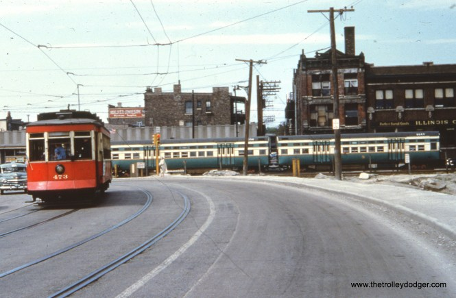 """This photo was marked as being taken in April 1951. Unfortunately, what the picture shows makes that date impossible. The buildings behind the ground level """"L"""" show that this is Western Avenue at Van Buren, during the 1953-58 rerouting of part of the Garfield Park """"L"""". Red car 473 is on a curve because the tracks are on a shoo-fly while the bridge that would go over the Congress (now Eisenhower) expressway was under construction to the left of this view, which looks north. This phase of construction, and the presence of car 473, would imply that this picture actually dates to May 16, 1954, when this car and 479 were used on a CERA """"farewell to red cars"""" fantrip on Chicago's streetcar system. Meanwhile, a two-car train of flat door 6000-series """"L"""" cars (6049-6050), with numbers painted on their roofs, proceeds on the ponderously slow 2.5 mile temporary trackage."""