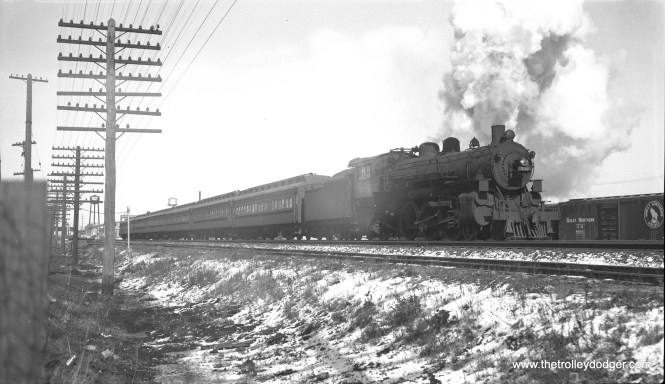 """In the twilight days of steam, C&NW locomotive 532, a 4-6-2, heads a commuter train in February 1956. Although this negative is marked as having been taken at Euclid Avenue in Oak Park, where UP freight and Metra commuter trains now share space with the CTA's Green Line rapid transit, this certainly looks like it was taken somewhere else at ground level. (Bob Selle Photo) Andre Kristopans: """"The CNW """"Euclid Ave"""" shot most likely is about where Kilpatrick Av now crosses the tracks. If one blows up the photo, you see a railroad overpass in the background that certainly looks like the BRC bridge at Kenton. Box cars on right would be on one of the tracks at 40th St Yard, while the lower-level track in foreground would be an industrial lead. Train would be EB."""""""