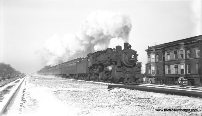 """Chicago & North Western loco 608, a 4-6-2, heads an eastbound commuter train at Oak Park Avenue on March 23, 1955. This shows how the wide C&NW embankment made it possible, within a few years, to elevate the outer end of CTA's Lake Street """"L"""". In the process, several close-in C&NW stations were closed. (Bob Selle Photo)"""