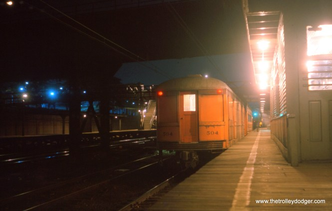 """I believe this July 1963 picture shows the South Shore Line station at Roosevelt Road. Frank Hicks writes, """"Chicago South Shore & South Bend 504. This interurban freight trailer has a more unusual history than most. It was built for ISC as an interurban combine, and ran on that system's lines in Indiana for five years until ISC became part of the great Indiana Railroad system. IR rebuilt the three cars of the 375-377 series into railway post office cars and put them to use in this unusual capacity. The three RPO's survived on IR until the end of interurban service in 1941, at which time all three were sold to the only other interurban line then operating in Indiana: the South Shore. The South Shore converted 376 into a line car while 375 and 377 became express package trailers. These cars were designed to run in passenger trains and had control lines so that they could be run mid-train; they were often used to transport newspapers. Car 504 was retired in 1975 and acquired by IRM, which has repainted it and put it on display."""" (Editor's Note: car 377 became 504.)"""