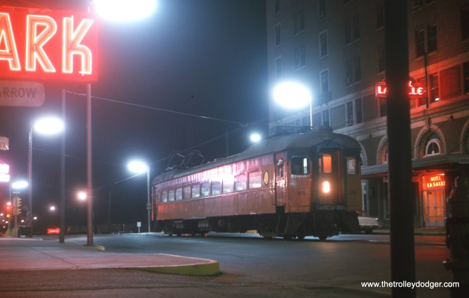"In this classic July 1963 shot, South Shore Line car 25 is parked at the east end of the line in downtown South Bend, across from the Hotel LaSalle. Service was cut back to Bendix at the outskirts of town in 1970, and later extended to the local airport. Don's Rail Photos adds, ""25 was built by Pullman in 1927. It was lengthened and air conditioned, and got picture windows in 1947."""