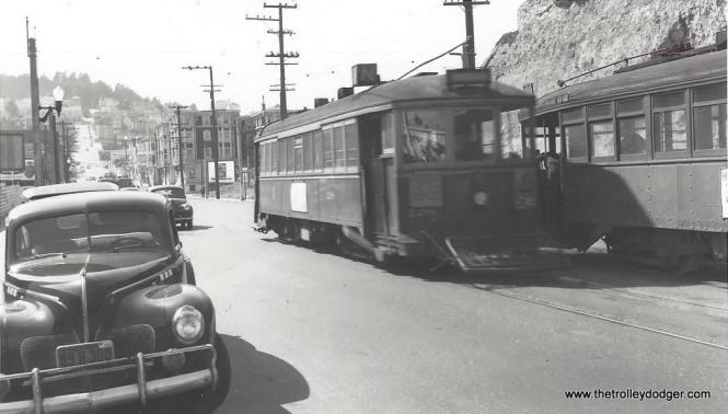 "Tony Manthos: ""Here is the photo of no. 128. I am hoping that this is San Diego Elec. Ry. 128 (St. Louis Car Co. 1912). I understand the series had centre doors but they were removed in 1924. I can't read the signs on the side and front. The car on the right seems to have the same sign, but only the H of the first word is visible. The box-like appendage on the roof seems to be a feature of SD cars. The flame shaped streetlight globes are distinctive. Are they a SD feature? There are 5 trolley cars in the picture, which seems a lot for a relatively quiet street. My big question is this - No. 128 and some others were apparently sold to make private residences around1937, but the California license plate on the auto has a 1948 tag in the corner. I hope you can make sense of this. Many thanks."" Don Ross: ""The 128 was Municipal Ry of San Francisco."" Tunnelstation writes: ""The cars you think are SD cars are indeed San Francisco Municipal Railway streetcars. The location is on Duboce Street passing the ""New"" Mint just off of Market street. In the background is where the Sunset Tunnel (built in 1928) is located, which took the Muni cars through the hills to the Inner Sunset District on their way to the Beach and the Pacific Ocean where the ""N"" Judah Street line ended in a loop."""