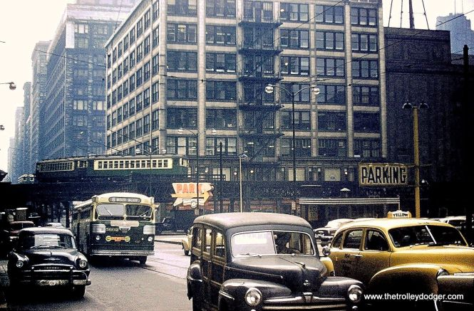 """In this 1950s photo, CTA bus 5602 is on route 6. Meanwhile, we see trains of 4000s and 6000s on the """"L"""" at Wabash and Lake. From 1913 to 1969, trains on both tracks ran in a counterclockwise direction. George Trapp: """"Bus 5602 is on route 6, Garfield Blvd not Van Buren. The 5500 series propane buses didn't start to arrive until late 1953. Garfield route was one of the first routes transferred away from a former CMC garage, 52nd to Ashland-69th. Propane 5500's were a downgrade from CMC Diesels which were faster, easier to see out of and had more comfortable mohair plush seats."""""""