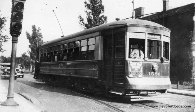 """It's not easy to determine just where this picture of CSL 1589 was taken on August 4, 1934. The car is signed for Irving Park and Neenah, and with the track configuration, you would expect we are at the east end of the Irving Park line. However, according to my CSL track maps, the crossover was just west of Broadway. If so, that doesn't explain the traffic signal in the picture. Perhaps Irving Park cars turned back just east of Broadway? (Earl W. McLaughlin Photo) Andre Kristopans: """"More likely Irving and Clark. Note cemetery behind car."""""""