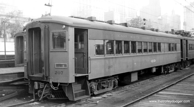 """Caption: """"Chicago, South Shore and South Bend trailer 207. Although this car has no motors, it has controls, and can be used as (the) head car in (a) train. These trains make the 90 miles to South Bend in 2 hours and go over 100 to keep up schedule, and they go through city streets in several cities, among them Gary. They use tracks of the Illinois Central out and in Chicago. Builder- Pullman."""""""