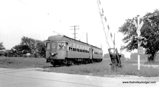CA&E 134 and 137 under wire at State Road crossing on the Batavia branch, August 30, 1942. The flags would seem to indicate this was CERA fantrip #39. Wire was used here for a short distance instead of third rail, due to the width of the crossing.
