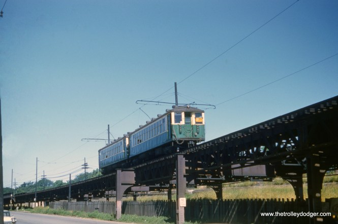 "A two-car train of CTA 4000s goes up the ramp toward the Laramie station on the Lake Street ""L"" on July 5, 1960. The portion of the line west of here was relocated onto the nearby Chicao & North Western embankment on October 28, 1962. Earlier that year, power on the ramp was changed from overhead wire to third rail, to facilitate the transition."