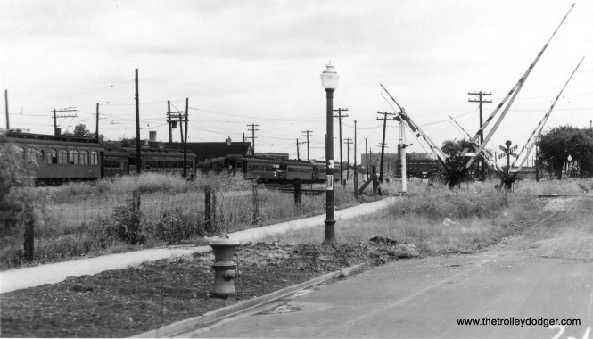 """Here is a different angle than we are usually used to seeing of the CA&E Wheaton Yards. Cars 315 and 415, among others, are present. On the other hand, Jack Bejna writes: """"The photo that you labled a different view of the Wheaton Yards is probably a view of the Laramie Yards taken from a different angle (looking northeast). The crossing is probably Lockwood Avenue and the view is generally toward the tower. Zoom in the image and under the short part of the gate you can see the top half of the tower. In addition, the dark building has 6 short windows and two long windows. The photo I've attached was labled Lockwood Yard and shows the same building as well as the top of a radio tower and a water tower in the background (you can see both in your recent photo)."""""""