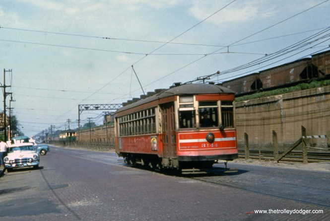 """CTA one-man streetcar 3144 heads east on Route 16 - Lake Street somewhere between Laramie and Pine Street, while a two-car train of 400-series """"L"""" cars runs at ground level parallel to the streetcar. The time must be near the end of red car service here, which was May 30, 1954, as that is a 1953 or 1954 Cadillac at left. The C&NW signal tower on the embankment is still there today, at about Pine Street, which is where streetcars crossed the """"L"""" to run north of the embankment for a few blocks before terminating at Austin Boulevard, the city limits."""