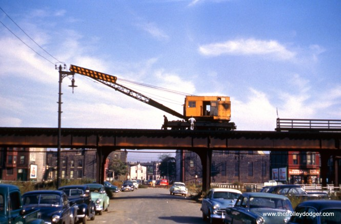"""This picture shows a CTA crane in operation on the old Metropolitan or Garfield Park """"L"""" in the early 1950s. You can see how many nearby buildings have already been cleared away in order to build the Congress Expressway."""