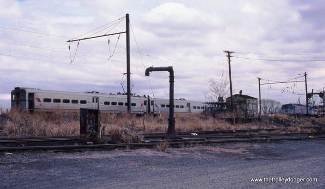 Photo 19. PRR K-4 steam locomotives once quenched their thirsts here at the South Amboy engine terminal. In 1987 it was NJT MUs and E-60s that got the attention. Arrow III #1399 is seen behind the steam-era water column.