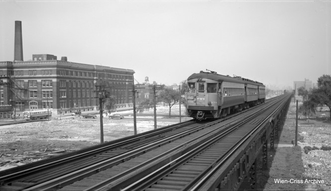 """CA&E 458 heads a three-car train westbound at Western Avenue. The CTA bus on Van Buren indicates that this picture was taken no earlier than August 12, 1951. The Van Buren Street temporary trackage appears to be in place already, but testing has not started yet, as there are barriers in place. """"L"""" service shifted to the temporary trackage in September 1953 and the CA&E cut back service to Forest Park. At left you can see the imposing structure of Richard T. Crane Medical Preparatory High School, otherwise known as Crane Tech. We are looking to the east. (Robert Selle Photo, Wien-Criss Archive)"""