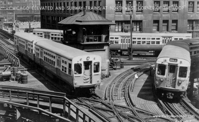 """Three CTA trains of 6000-series """"L""""/Subway cars are lined up by the old Tower 18 in the early 1950s. As you can see, with the tower in the middle of the junction, not all moves could be made. For example, eastbound trains coming from Lake Street could not go straight east, but had to turn south. At this time, traffic on both the inner and outer Loop tracks went in the same direction (counter-clockwise). This arrangement was changed in 1969 when the CTA wanted to through-route Lake with the new Dan Ryan line. The tower was moved and replaced with a new one, and new eastbound trackage was built where the old tower was. That was also the beginning of bi-directional operations on the Loop, which continue to this day."""