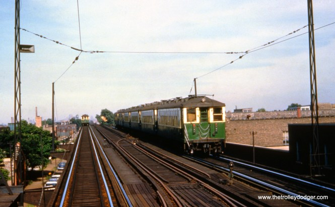 """""""Chicago, IL. CTA car #4333 brings up the rear of an eastbound Lake Street """"L"""" train. View looks east from Lake/Laramie station. Note pull-offs for overhead trolley wire, used west from Laramie station. June 23, 1959,"""""""