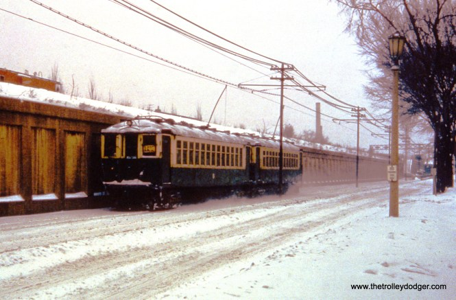 """""""Oak Park, IL. A pair of 4000s, working a westbound trip on CTA's Lake Street """"L"""", are on South Boulevard at Kenilworth Avenue. Visible in distance (on embankment) is one-time """"Avenue"""" Chicago & North Western passenger station, located at Oak Park Avenue. View looks east on January 18, 1962."""""""