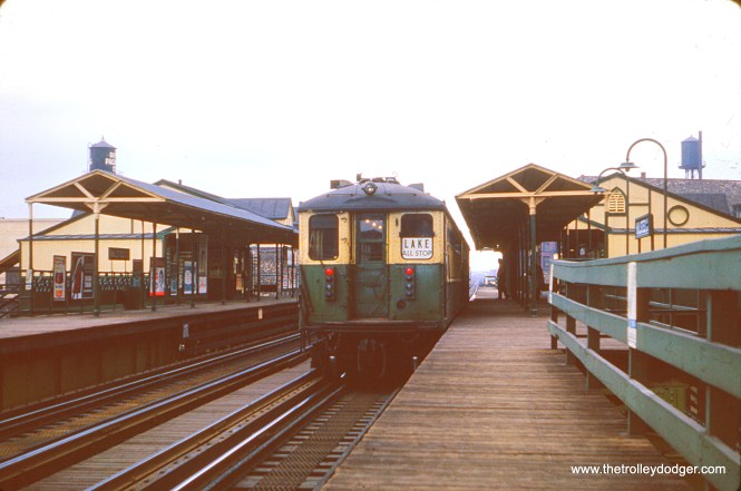 "In this picture, taken in April 1964, we see the back end of a CTA two-car train of 4000s as they head east at Halsted on the Lake Street ""L"". By this time, the western portion of the line had been relocated onto the C&NW embankment, and therefore there was no further need to use overhead wire. But the new 2000-series ""L"" cars had not yet replaced the 4000s in this line, which they would do shortly. This station, built in 1892-93, was closed in 1994 for the Green Line rehabilitation project, but never reopened. It was demolished in 1996 and the new Morgan station, two blocks to the west, more or less replaced it when it opened in 2012."