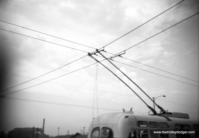 """It's not clear where this picture was taken. The two wires that cross the trolley bus wires are, I am told, """"feeder span hangers."""" The last Chicago trolley bus ran in 1973. The CTA currently has two electric buses that run on batteries, and has just placed an order for 20 more."""