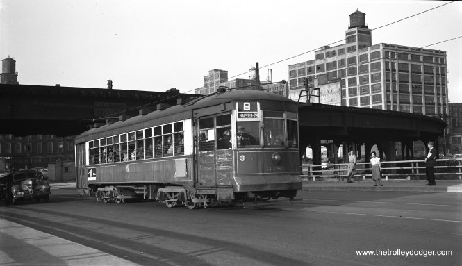 """CTA two-man arch roof car 3189 is southbound on Halsted Street near the Garfield Park """"L"""" overpass, south of Van Buren Street on September 17, 1953. As had previously happened with 63rd Street, PCCs had been taken off this route and replaced by older red cars for the final few months of service. 3189 is on the bridge that would eventually go over the Congress expressway, which was then under construction. (Robert Selle Photo)"""