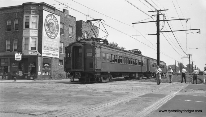 On August 28, 1955 Illinois Central Electric suburban 1161 and its trailer are crossing Halsted Street at 121st on their way to Blue Island. There was a fantrip that day (hence the fans,), but this was not the fantrip train apparently. (Robert Selle Photo)
