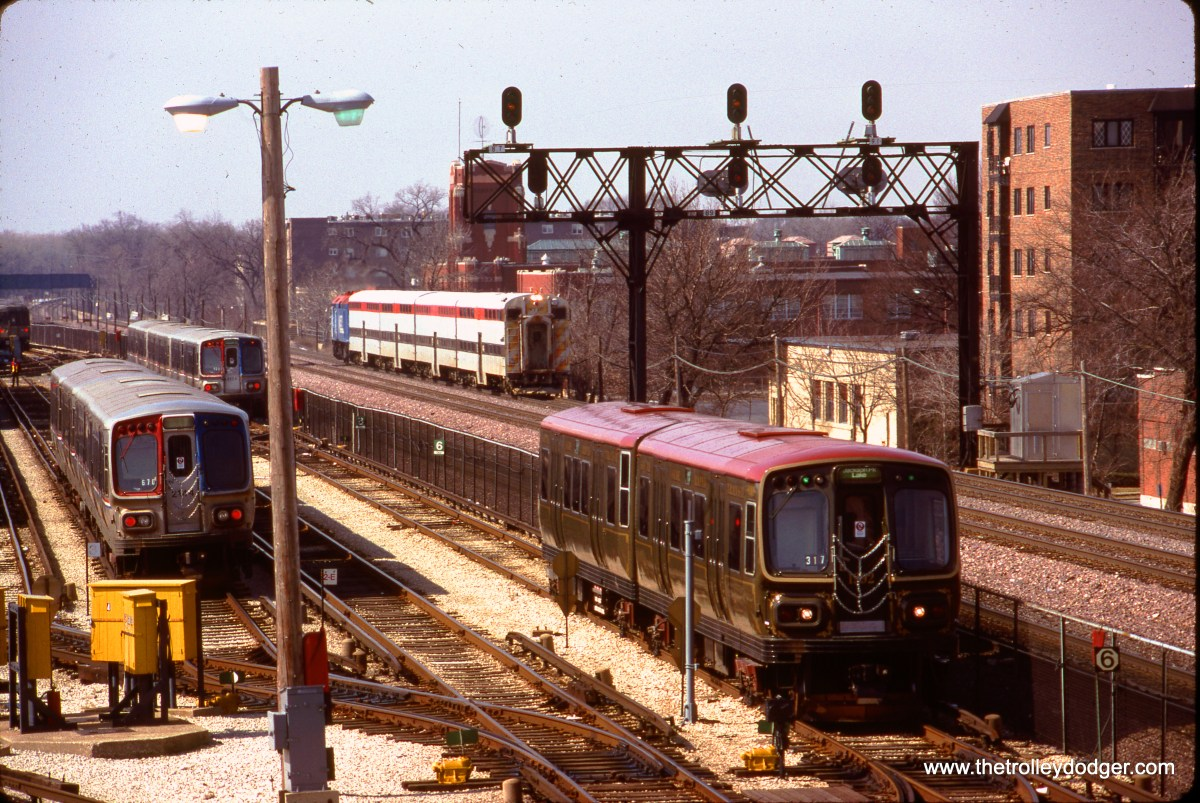 """The CTA has a yard for the Green Line (formerly the Lake Street """"L"""") just west of the Harlem Avenue terminal in suburban Forest Park. Here, various cars in the 2000-series are seen, along with a Metra commuter train on the adjacent Union Pacific West Line. This picture was most likely taken during the 1990s. (Bruce C. Nelson Photo)"""