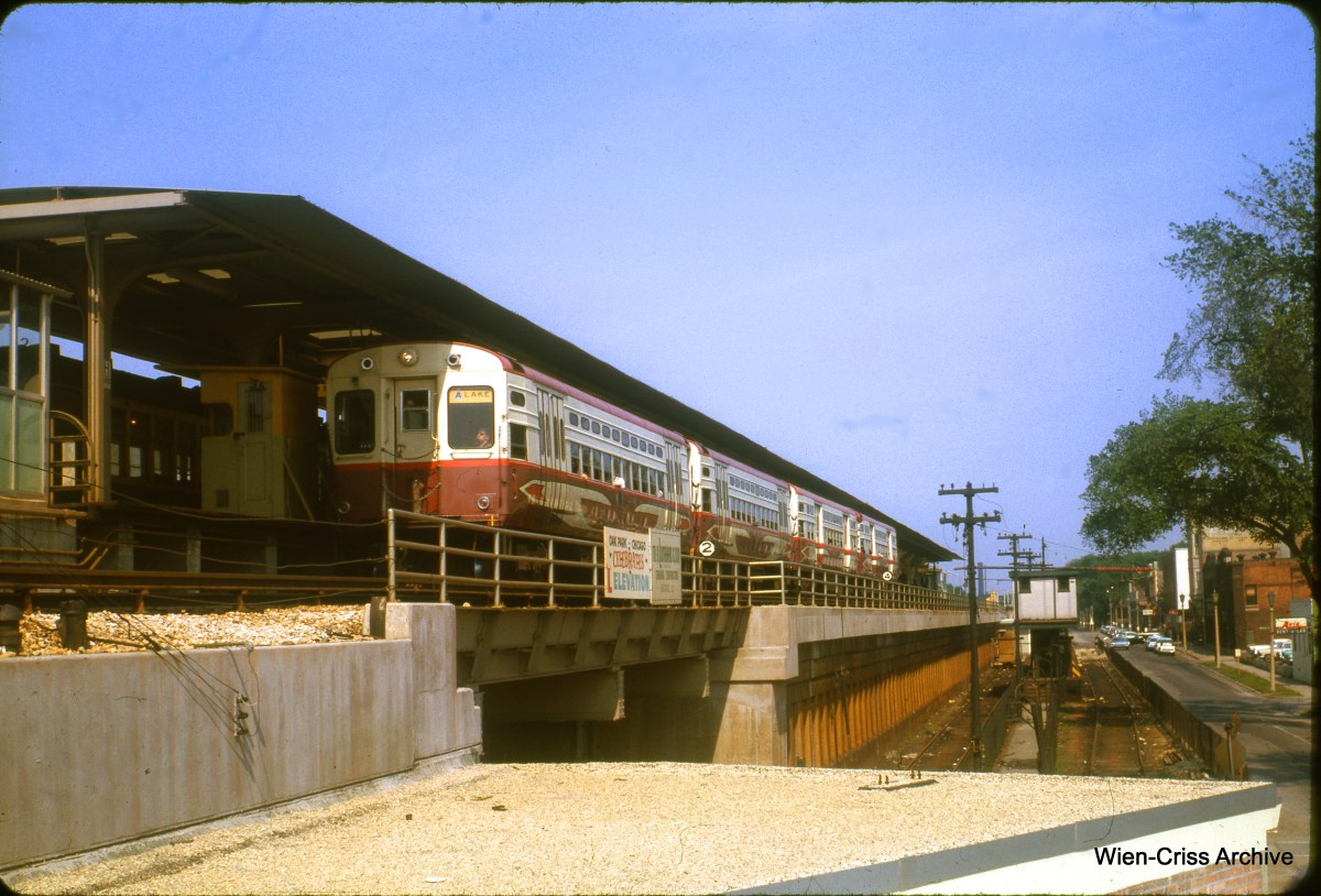 """It's June 1963, several months after the CTA elevated the Lake Street """"L"""" onto the Chicago & North Western embankment. A four-car train made up of """"circus wagons,"""" the fan's name for experimental high-speed cars, is making a rare appearance at Harlem Avenue, the end of the line. This view looks east. (Wien-Criss Archive)"""