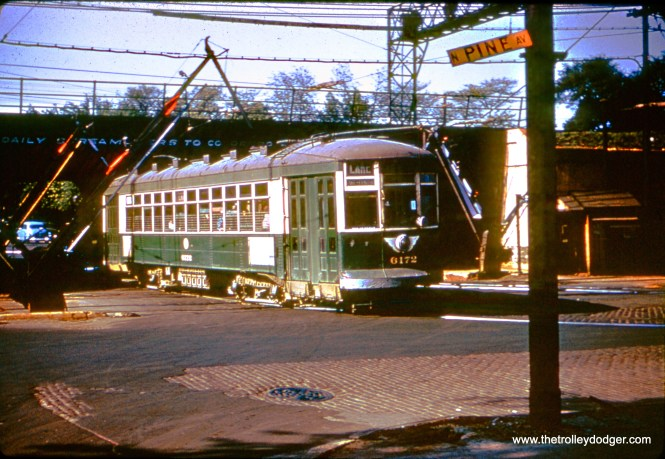 In the last couple years of red car service in Chicago, which ended in 1954, the CTA painted a few of the older streetcars green. It was not an attractive color for them. Here, we see inbound car 6172 jogging from one side of Lake Street to another via Pine Avenue. To this day, tracks are still visible under the viaduct. At this point, streetcars crossed the Lake Street