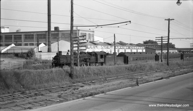 Chicago & North Western steam locomotive 511, a 4-6-2, is northbound at the EJ&E (Elgin Joliet & Eastern Railway) overpass in North Chicago, IL on the afternoon of July 13, 1955. In the foreground, we see the tracks of the Chicago North Shore & Milwaukee, the North Shore Line. North Chicago was also the original home of the Illinois Electric Railway Museum, which relocated to Union in the early 1960s. (Robert Selle Photo)