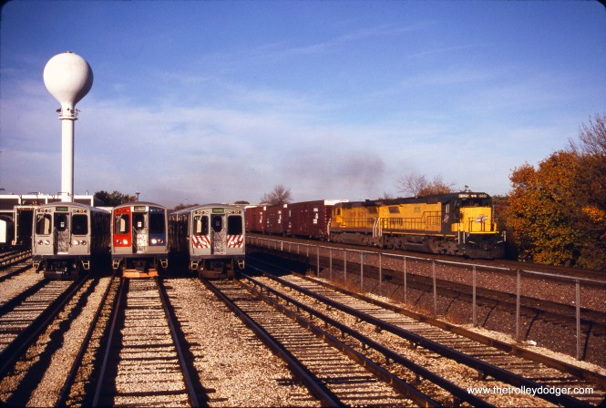 On October 20, 1996, a C&NW freight train passes some CTA 2400s (2457, 2512, and 2410) in the Green Line yard in Forest Park. (Bruce C. Nelson Photo)