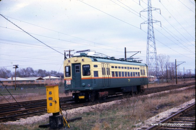 "The date stamped on this slide is April 18, 1964, when demonstration rides were given out on the new CTA Skokie Swift branch line. However, that date may be incorrect, as my understanding is on that day, single car units 1-4 were coupled together and operated as a unit to provide demonstration rides, Regular service began on April 20, 1964. So either the units were uncoupled, or the date is wrong. Here, one of the high-speed cars is lowering its pan trolley, at the point where the line changed from overhead wire to third rail ""on the fly."""