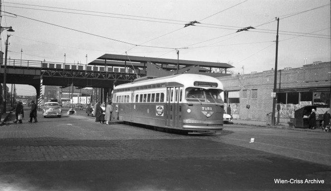 "You would be forgiven for not recognizing this location, but that's the Western Avenue station on the Humboldt Park ""L"", just north of North Avenue. The station was closed in 1952, probably just a few months before this picture was taken. If the station was open, there would be a sign advertising this, similar to ones seen in some of the other pictures in this post. You can also see trolley bus wires, used on North Avenue. PCC 7151 is a two-man car, and passengers are boarding at the rear. This portion of the old Humboldt Park line was not demolished for another decade, and the story goes that it would have been used by Chicago Aurora & Elgin interurban trains as a midday storage area, if service on that line could have continued after 1957. A cropped version of this photo ran in one of our earlier posts, but this was scanned from the original negative. (Wien-Criss Archive)"