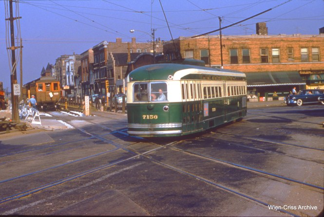 "CTA 7156, sporting unusual yellow numbers, is on Western at Van Buren on August 13, 1954. A wooden Garfield Park ""L"" train is nearby, on temporary trackage. At this stage, it appears the Western Avenue bridge over the Congress Expressway was not yet finished, as the streetcar (and auto traffic) are using a shoo-fly. (Wein-Criss Archive)"