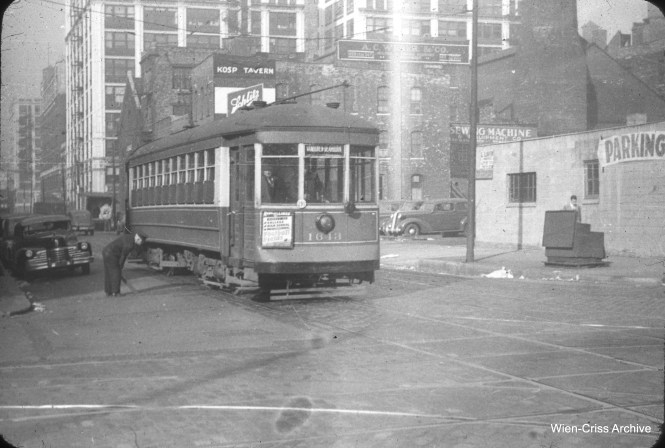 On October 15, 1948, the conductor of CTA 1643 (running on the Van Buren Street route) is holding a switch lever at the southwest corner of Van Buren and Clinton. (William C. Hoffman Photo, Wien-Criss Archive)
