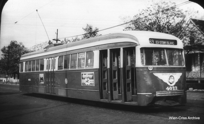 "This picture of CTA 4022 appears to show it set up for one-man service on 63rd Street, although this was not implemented, after two public hearings were held. These cars were instead used on Cottage Grove. Red streetcars were temporarily returned to 63rd, and then buses were substituted in 1953. (William C. Hoffman Collection, Wien-Criss Archive) On the other hand, Tony Waller writes, ""Hi, I have a few comments/corrections for the latest set of photos: Pic.736 shows a two-man pre-war PCC operating on 63rd St. In the middle of the car you can see two center doors, one was removed as part of the one-man conversion process. Also CTA would not be operating a one man car in the middle of an otherwise two-man route. In the recent CERA color-photo PCC book, as well as several of the Shore Line Interurban Society publications, there are photos of pre-war PCCs painted in the new Evergreen and Cream color scheme operating on 63rd St. The paint job was done as part of the advance work for the one-man process to keep the PCCs operating on 63rd as long as possible. The conversion process would require that the whole fleet to be removed from service; removing one of the center doors and the conductor's station and replacing them with additional seats, relocating all door controls to the motorman's position, removing Chicago's unique hand operating controls and replacing them with the standard (i.e., nationwide) foot operating controls. The CTA's new ""big wings"" around the headlight denoting front entrance, one-man operation would not affect a repainted car in temporary two-man service as the pre-war PCCs were always front entrance anyway. Those post-war PCCs converted to one-man and those ""Sedans"" so converted (but never used) also got the ""big wings."""""