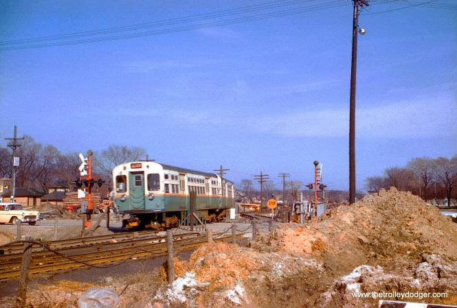 "In this April 4, 1959 view, a westbound CTA Congress-Milwaukee ""A"" train crosses DesPlaines Avenue in Forest Park over temporary trackage. I-290 is under construction here, and this portion of highway opened in 1960. The tracks shown here were south of where the line crosses DesPlaines Avenue today. While there was once a grade crossing between the CTA and the B&OCT freight line, the two sets of tracks were grade-separated as part of the highway project, and just east of where this picture was taken, the CTA crosses the highway (and the freight tracks) on a flyover. This was not yet in use in April 1959, and the CTA used temporary tracks that were approximately where the westbound lanes of I-290 are today."