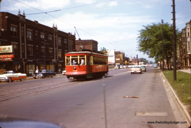 "Another picture of the final CTA streetcar fantrip on May 25, 1958. Red car 144 (now at the Illinois Railway Museum) is somewhere along the Wentworth line on Chicago's south side. (J. W. Vigrass Photo) Our resident South Side expert M. E. adds, """"Somewhere on the Wentworth line"" has to be along Vincennes between 81st and 73rd, and most likely between the 77th St. barn and 73rd. (At 73rd, the car line curved north onto Wentworth.) The street width of Vincennes was noticeably wider than the width of Wentworth."" The sequence of shots taken by the photographer would suggest the car is northbound. There is the Hamilton Park Laundry (7416 S. Vincennes) at the left of the picture. Hamilton Park is located just a few blocks west of Vincennes, between 74th and 72nd."