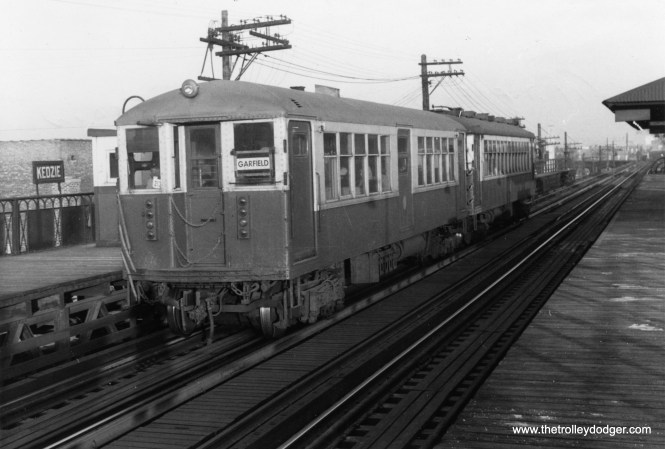"A Garfield Park ""L"" train of 4000s heads west at Kedzie on November 6, 1955. Unlike some other stations on the line, this one remained in service until 1958 as it was not directly in the expressway footprint. The first car is a ""Baldie,"" built circa 1915, and the second is a ""Plushie,"" from around 1924. These were state of the art cars when new, and were in service for nearly 50 years."