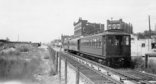 "CTA 2519, among others, form a three-car train at Van Buren and Ogden. This must be in the early days of the temporary Garfield Park ""L"" operation, since the old ""L"" is still standing at left. The portion to Paulina (1700 W.) had to be kept until April 1954, as the Douglas Park ""L"" was still using it then. We are looking west at about 1800 W. Van Buren, and the ""L"" west of here was taken down pretty fast to facilitate expressway construction."