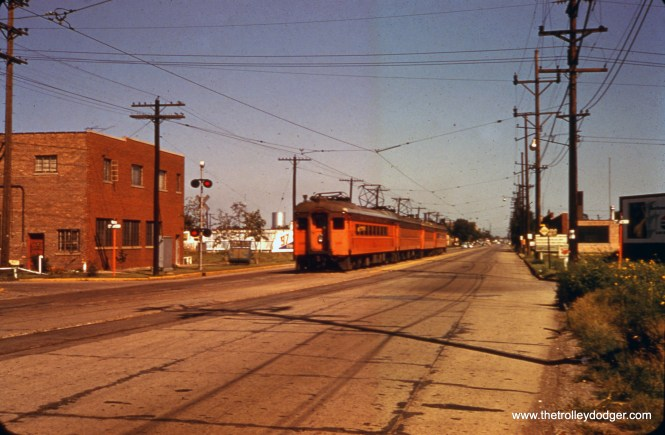 "The South Shore Line in East Chicago, Indiana, when it ran on the street. In 1956, this trackage was relocated to run parallel to the new Indiana Toll Road. Robert Lalich: ""Photo 683 was taken at White Oak and Chicago Ave in East Chicago. The train is WB and is about to curve to the north onto private right of way before crossing the B&OCT near Columbia Ave. Notice the unusual placement of flashers on the left to warn westbound motorists."""