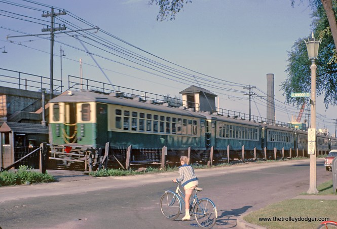 "CTA Eastbound Lake St. ""L"" going past the pedestrian-only grade crossing at Elmwood Ave in Oak Park, IL on August 14, 1962"