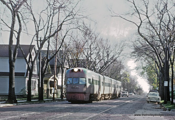 An Electroliner on the Milwaukee Streets -- 4 Photos I don't know how Roger Puta did it, but he photographed the same northbound Electroliner both on 5th and 6th Streets on October 21, 1962 only a couple blocks apart. Here are his captions. 1. CNS&M Train 805, The Electroliner on S. 5th St. approaching W. Orchard St. 2. CNS&M Train 805, The Electroliner on S. 5th St. near W. Orchard St. 3. CNS&M Train 805, The Electroliner coming out of private right-of-way onto S. 6th St. at W. Scott Ave. [Look who has the railfan seats. I don't remember. Are they looking at a blank wall?]